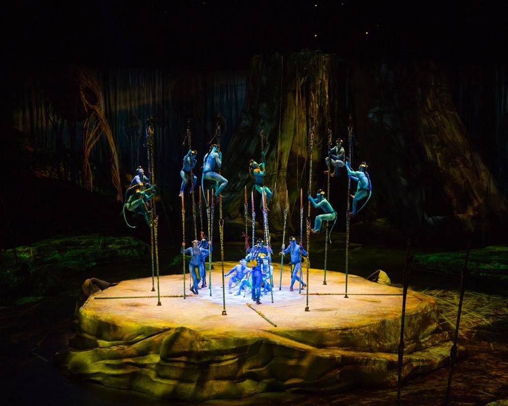 Cirque Du Soleilin Toruk teoksesta kuva, jossa sinisiin pukeutuneet Avatar-hahmot kiipeävät tolpissa